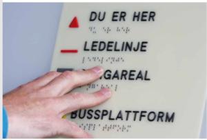 Foto av skilt med punktskrift og taktile bokstaver
