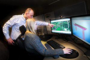 Foto av to personer som arbeider ved dataskjermer