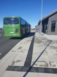 Foto av bussholdeplass med buss og ledelinjer samt oppmerksomhetsfelt