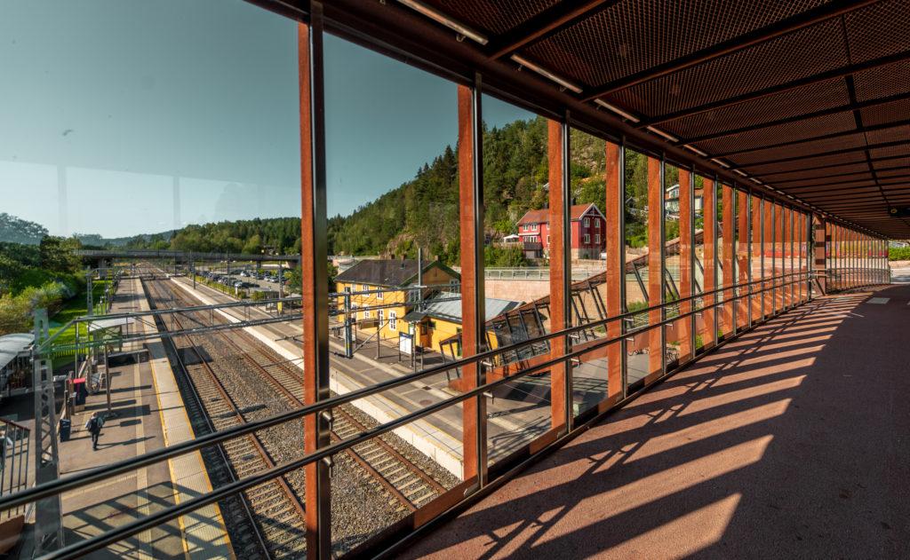 Gangbro over togspor, med vindu og utsikt ned mot perronger begge veier