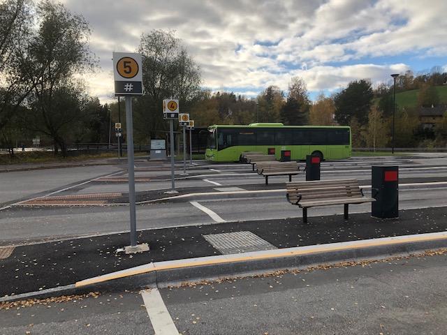 Bilde av en bussholdeplass, med en buss i bakgrunnen